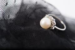 un anneau de perle sur le tissu de dentelle Photographie stock libre de droits