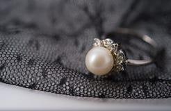 un anneau de perle sur le tissu de dentelle Image stock