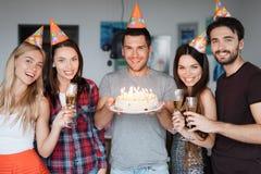 Un anniversaire du ` s de type et ses amis le félicitent Les invités se tiennent autour du garçon d'anniversaire Le type tient a Image stock
