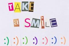 Un annuncio di carta con la frase: Prenda un sorriso e con i segni di sorriso Immagine Stock