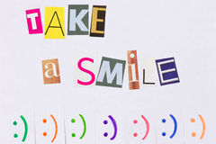 Un anuncio de papel con la frase: Tome una sonrisa y con las muestras de la sonrisa imagen de archivo