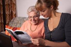 Un'anziana con un computer portatile Immagine Stock