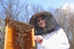 Un apicultor de la chica joven en colmenar Foto de archivo