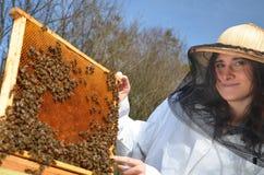 Un apicultor de la chica joven en colmenar Fotos de archivo