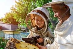 Un apicultor experimentado transfiere el conocimiento de la apicultura a un pequeño apicultor El concepto de transferencia de la  Foto de archivo libre de regalías