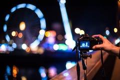 Un appareil-photo sur le trépied avec une main devant un fond noir avec des projecteurs Image stock