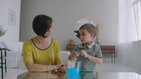In un appartamento bianco che si siede sulla mamma e sul ragazzo del pavimento usati per giocare un giocattolo stretchable del pl stock footage