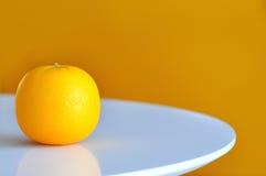 Un arancio sulla tavola rotonda bianca Fotografia Stock Libera da Diritti