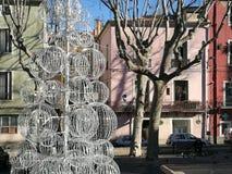Un arbre d'indigène a stylisé avec de grands bals blancs devant les bâtiments colorés à Sète dans les sud des Frances image stock