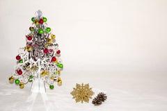 Un arbre de Noël argenté avec les décorations colorées Photos stock