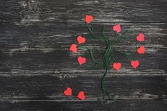 Un arbre vert fait à partir du fil de toile avec les coeurs rouges au lieu des feuilles sur un fond noir en bois Jour du `s de Va Photographie stock