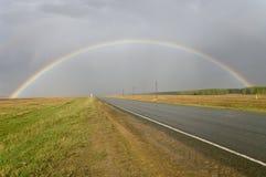 Un arc-en-ciel au-dessus d'une route. La Russie. Photographie stock libre de droits