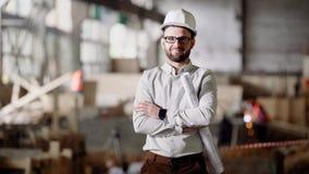 Un architecte adulte dans un casque se tient au chantier de construction actuel, dans des ses mains un projet pour la modernisati clips vidéos