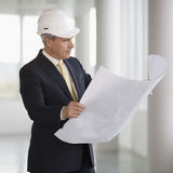 Un architecte utilisant un casque antichoc tenant des plans Photos stock