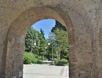 Un arco de piedra a un cielo verde del parque Foto de archivo