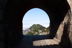 Un arco della pietra dà un parere di uno dei picchi della sommità del ` s di Tai Shan nella provincia di Shandong, Cina Fotografie Stock