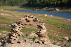 Un arco delle rocce impilate vicino ad una riva del lago immagini stock libere da diritti