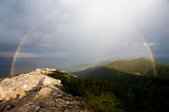 Un arco iris en las montañas Fotos de archivo