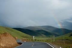 Un arco iris sobre el camino en las montañas, Tíbet, China Fotos de archivo libres de regalías