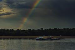 Un arcobaleno da un buio si rannuvola un fiume e una nave del motore fotografia stock libera da diritti