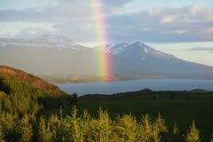 Un arcobaleno sopra le montagne innevate l'islanda fotografie stock libere da diritti