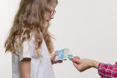 Un argent de poche La maman donne à l'enfant l'argent liquide photo stock