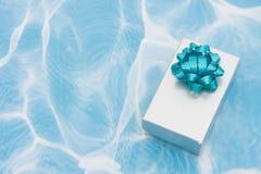 Un argento presente con l'arco sulla priorità bassa del aqua Fotografia Stock