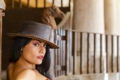 Un'aria aperta castana ispana adorabile del cavallo di Poses With A del modello in un ambiente familiare fotografia stock