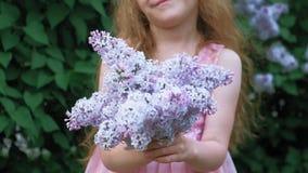 Un'aria aperta della bambina in un parco o in un giardino tiene i fiori lilla Cespugli lilla nei precedenti Estate, parco archivi video