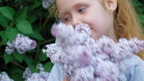 Un'aria aperta della bambina in un parco o in un giardino tiene i fiori lilla Cespugli lilla nei precedenti Estate, parco video d archivio