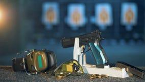 Un arma, auriculares, revista y balas presentados en la tabla en una galería que enciende almacen de metraje de vídeo