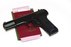 Un arma, un pasaporte y un dinero de la mano fijaron en una base blanca del fondo Imágenes de archivo libres de regalías