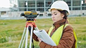 Un arpenteur de jeune femme dans les vêtements et le casque de travail ajuste l'équipement et produit des calculs sur la construc clips vidéos
