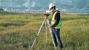 Un arpenteur masculin dans des vêtements de travail ajuste l'équipement sur le chantier de construction Le concept de la concepti banque de vidéos