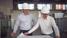 Un arquitecto del constructor del niño que mira planes del edificio, hablando al walkie de la película hablada, a la medición, al almacen de metraje de vídeo