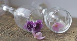 Un arreglo romántico de flores y de vidrios imagenes de archivo