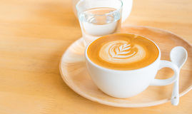 Un art de café de Latte sur le bureau en bois photographie stock libre de droits