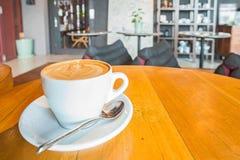 Un arte del café del Latte en el escritorio de madera en café Imagen de archivo