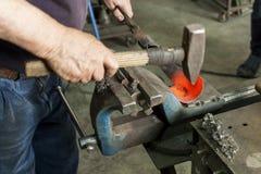 Un artigiano che lavora con un martello e un'incudine Fotografia Stock Libera da Diritti