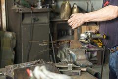 Un artigiano che lavora con un martello e un'incudine immagine stock libera da diritti