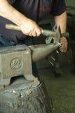Un artigiano che lavora con un martello e un'incudine Fotografie Stock Libere da Diritti