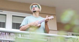 Un artista alegre juega el ukelele en el balcón en el verano almacen de metraje de vídeo