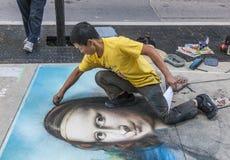 Un artista de la calle del pavimento dibuja a Mona Lisa en el asfalto Fotos de archivo libres de regalías