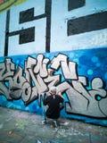 Un artista de la pintada, pintado en una pared gigante en la ciudad de París Fotos de archivo