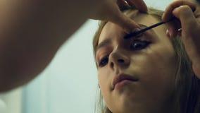 Un artista de maquillaje de sexo masculino pone maquillaje una mujer joven El amo habla del maquillaje para un grupo de muchachas almacen de video