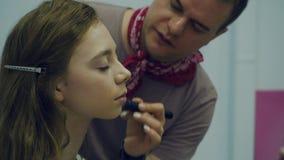 Un artista de maquillaje de sexo masculino pone maquillaje una mujer joven El amo habla del maquillaje para un grupo de muchachas metrajes