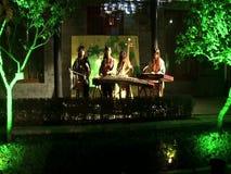 Un artista de sexo femenino que juega el Guzheng
