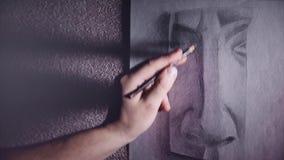 Un artista dell'uomo dipinge uno schizzo del gesso del naso con una matita della grafite video d archivio