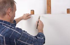 Un artista en estudio que piensa delante de la lona blanca imagenes de archivo