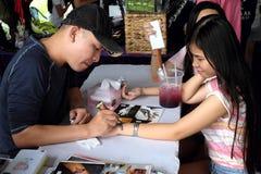Un artista está pintando algún tatto agradable a una chica joven Foto de archivo